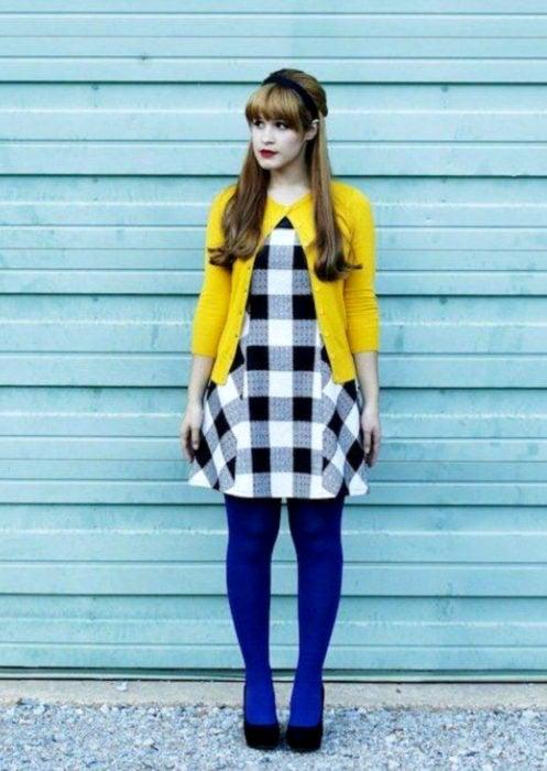 Outfits con medias de colores; chica con vestido blanco con cuadros negros, suéter amarillo y medias azul rey
