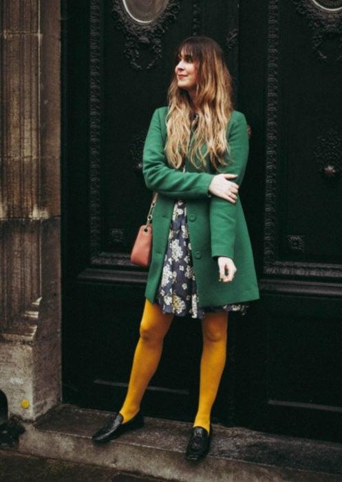 Outfits con medias de colores; chica posando frente a puerta,, con medias amarillas, vestido de flores y saco verde