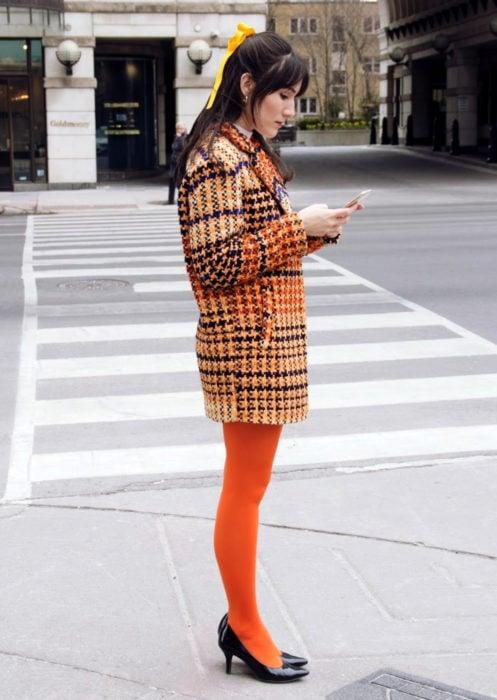 Outfits con medias de colores; chica con medias anaranjadas y con saco de cuadros, mirando su celular en la calle