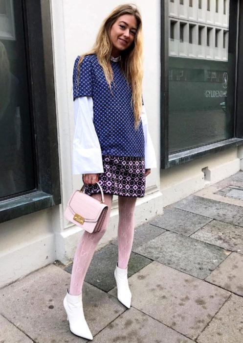 Outfits con medias de colores; chica rubia con medias rosas pastel y botas blancas