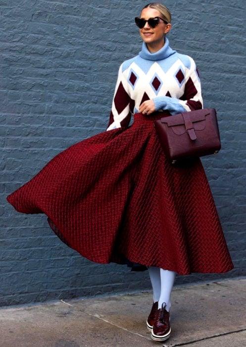 Outfits con medias de colores; mujer rucia con lentes de sol en forma de corazón, suéter oversized de rombos, falda midi rosa, medias azules y zapatos de charol color vino