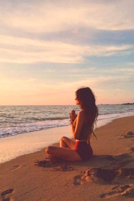 Mujer haciendo meditación en la playa