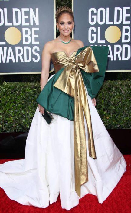 Jennifer Lopez en la alfombra roja de los Golden Globes 2020 con un vestido blanco y listón verde