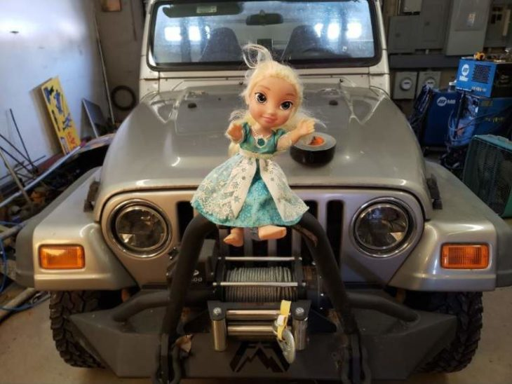 Muñeca Elsa sujetada al frente de un camión Jeep