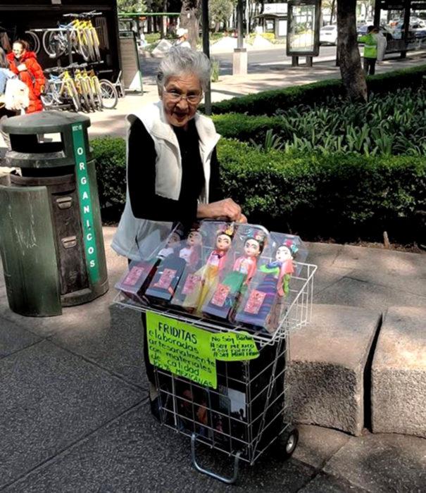 Viejita vende muñecas artesanales de pintora mexicana Frida Kahlo, en CDMX