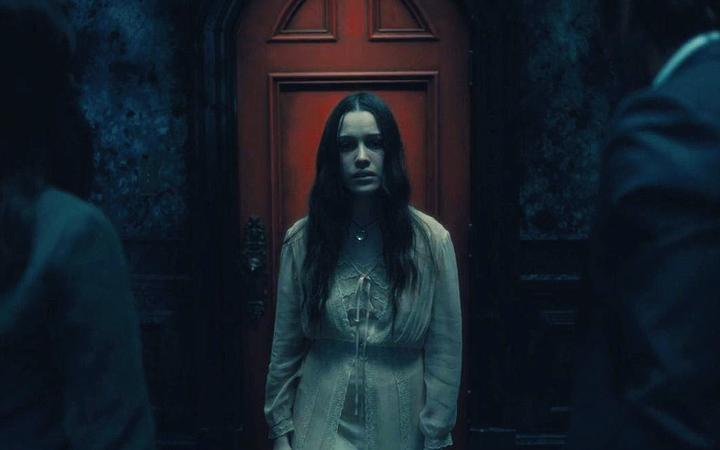 Nell Crain frente a la puerta roja en The Hill House