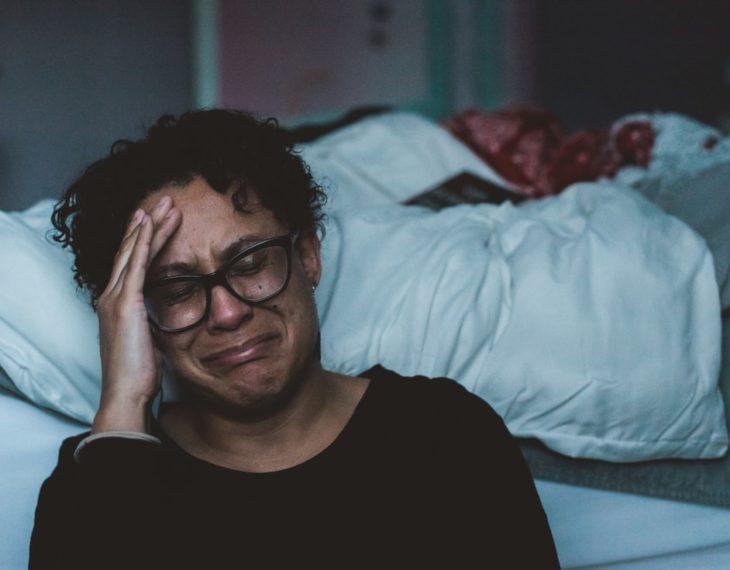 Mujer de lentes y cabello croto llorando en su habitación