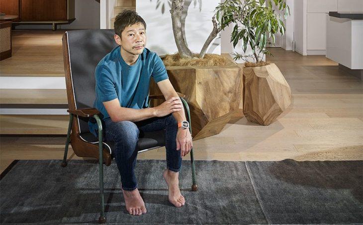 Yusaky Maezawa sentado en un sofá sin zapatos posando para una foto