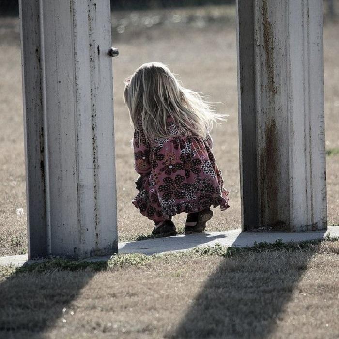 Niña pequeña rubia de espaldas sola entre dos postes