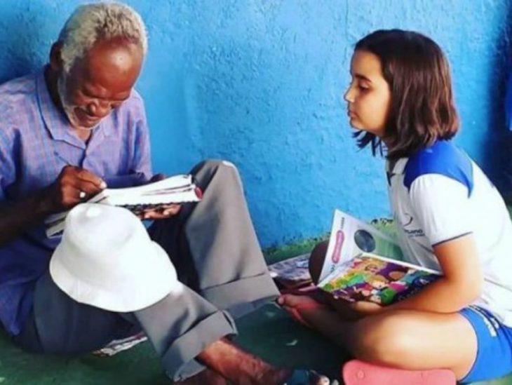 Bárbara Matos y Francisco Santana Filho leyendo, niña y señor de los helados sentado en la acera de la avenida