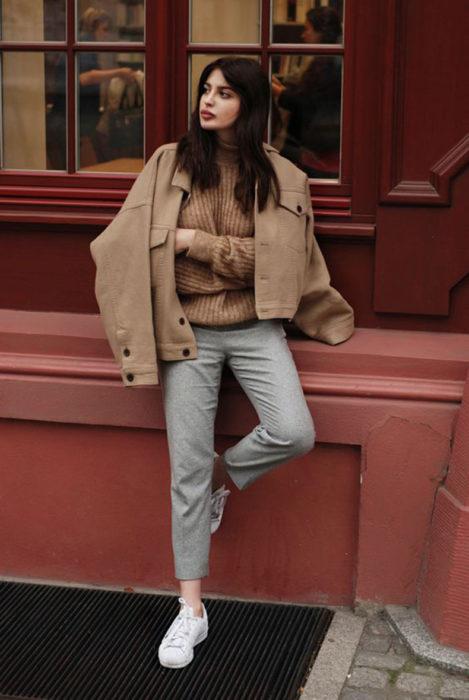 Chica modelando una chaqueta color arena a juego con pantalones ajustados en tono gris