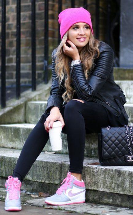 Chica llevando outfit en tono negro con tenis y gorro en rosa fucsia
