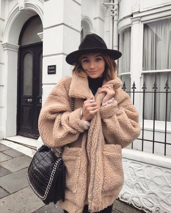 Chica llevando suéter afelpado en tono camel y sombrero en tono vino