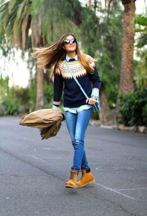 Chica a mitad de carretera modelando un suéter con diseño en triángulos