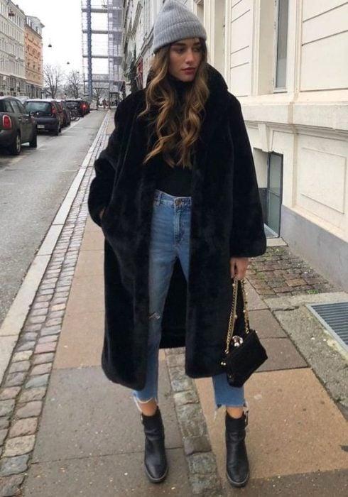 Chica con abrigo hasta las rodillas en tono negro y afelpado