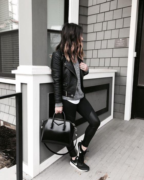 Chica llevando chamarra de cuero en negro y pantalones ajustados