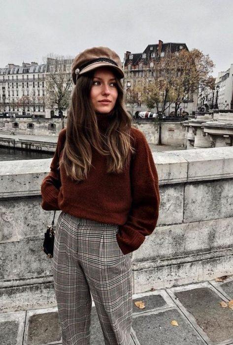Chica con outfit estilo francés a cuadros y boina a juego
