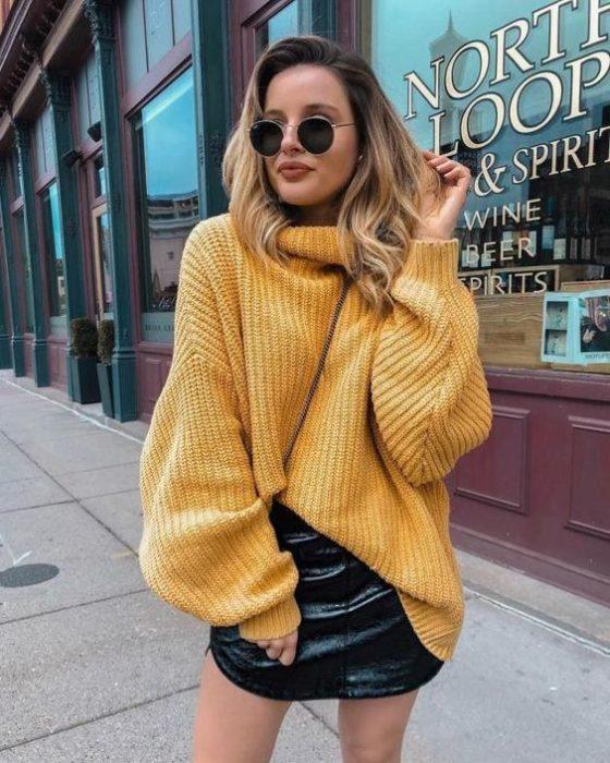 Chica llevando suéter oversize en tono mostaza para el frío