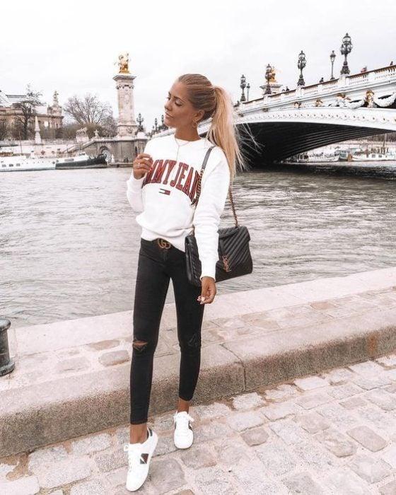 Chica lelvando outfit con sudadera blanca y jeans negros