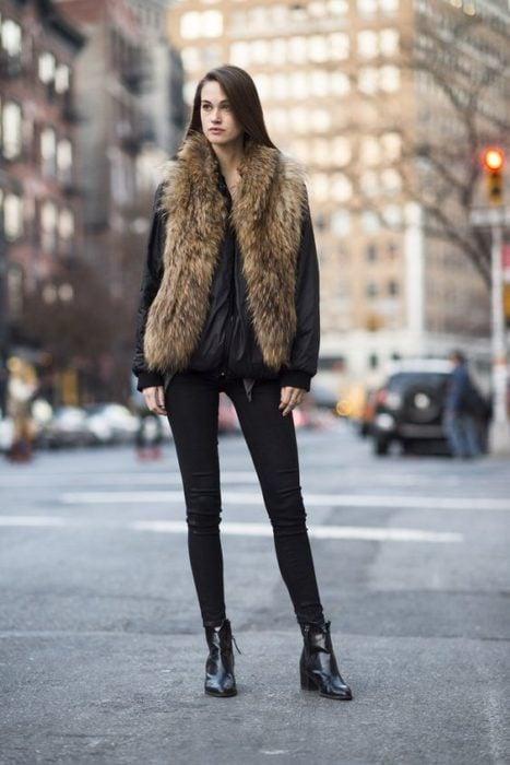 Chica modelando chaleco afelpado en tono café y jeans negros