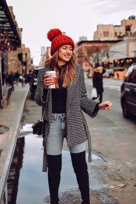 Chica llevando botas altas con skiny jeans y suéter a cuadros