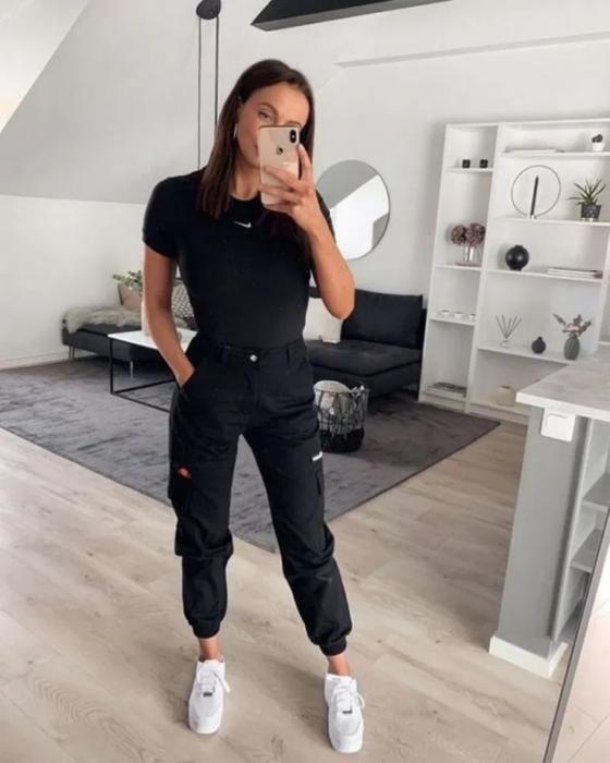 Chica con un jogger de color negro, blusa negra y tenis