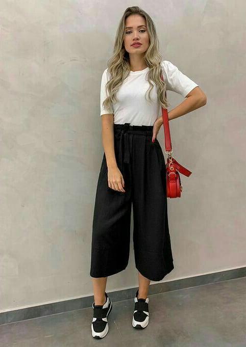 Chica con un pantalón estilo palazzo, blusa blanca y tenis