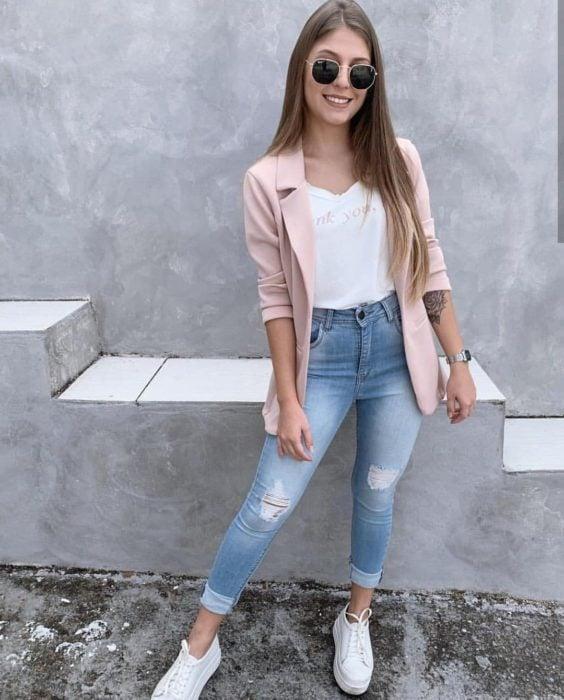 Chica con un outfit de jeans, blazer y blusa rosa con tenis de color blanco