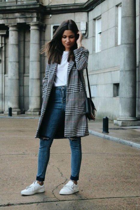 Chica con un saco, jeans y tenis de color blanco