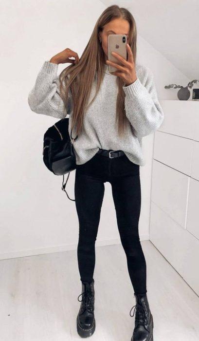 Chica con jeans negros, blusa gris y botas dr. marteens