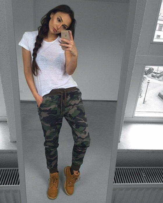 Chica con botas timberland, jogger de estilo miliar y blusa de color blanco