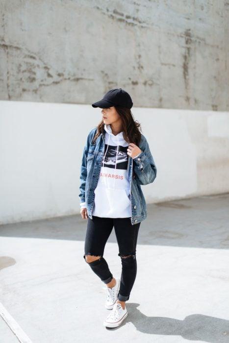 Chica con jeans, sudadera, gorra y chamarra de mezclilla