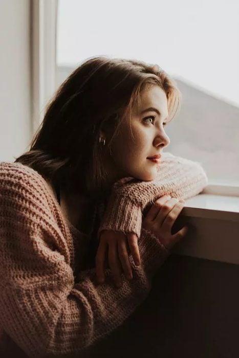 Mujer recargada sobre ventana mirando hacía afuera, vistiendo un suéter rosado