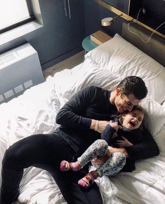Papá e hija recostados en la cama riendo