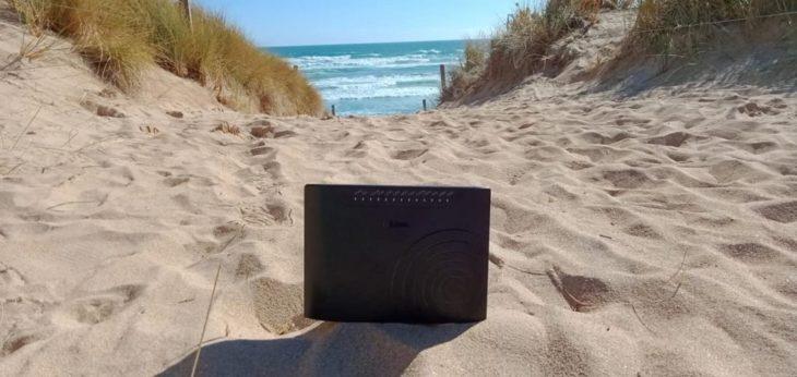 Módem de internet colocado en la arena mientras mira el mar