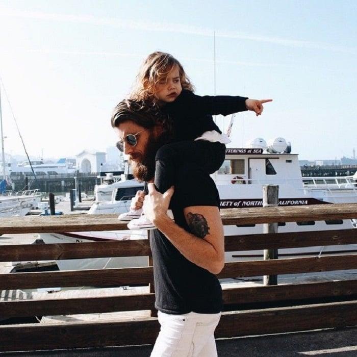Padre cargando a hija de caballito por muelle