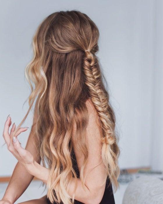 Peinados para San Valentín; cabello ondulado y rubio, con peinado de media cola con trenza de espiga