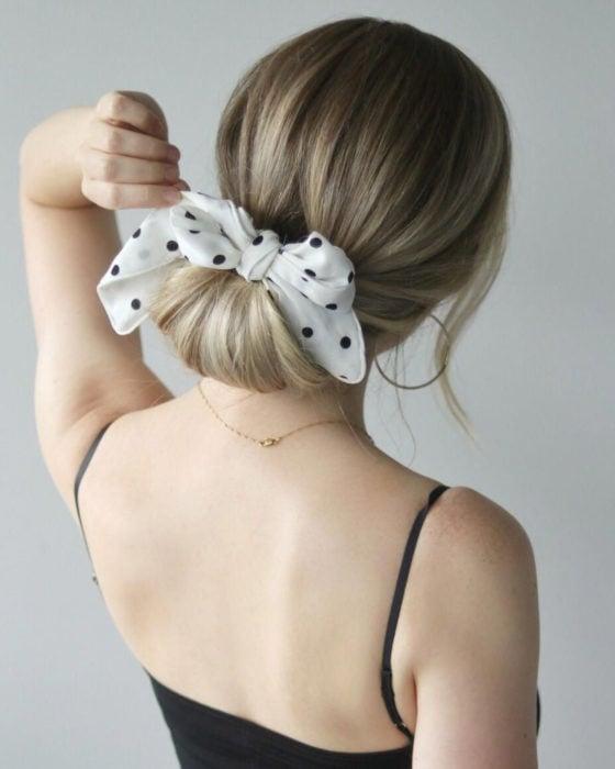 Peinados para San Valentín; cabello rubio recogido con un chongo bajo con un pañuelo blanco de lunares negros