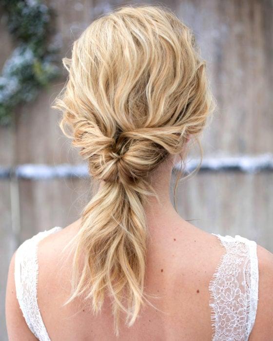 Peinados para San Valentín; mujer de cabello rubio, ondulado, peinado de cola baja con twist