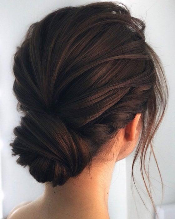 Peinados para San Valentín; cabello castaño con chongo bajo, elegante con twist