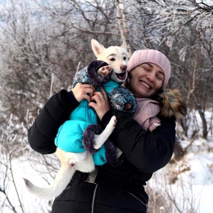 Betty, la perra con cejas; mujer cargando a cachorra blanca y de orejas paradas con suéter en la nieve