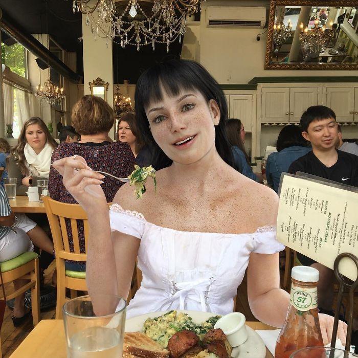Mujer sentada en un restaurante comiendo mientras luce como un maniquí