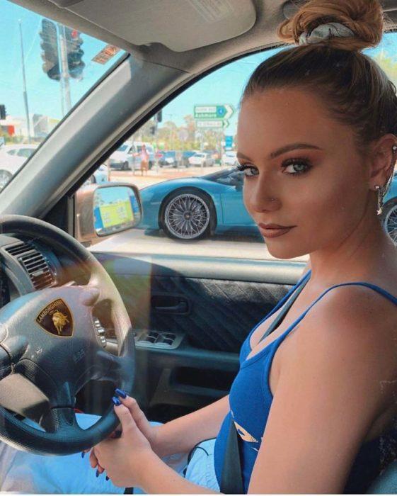 Chica sentada en su auto presumiento que se trata de un Ferrari