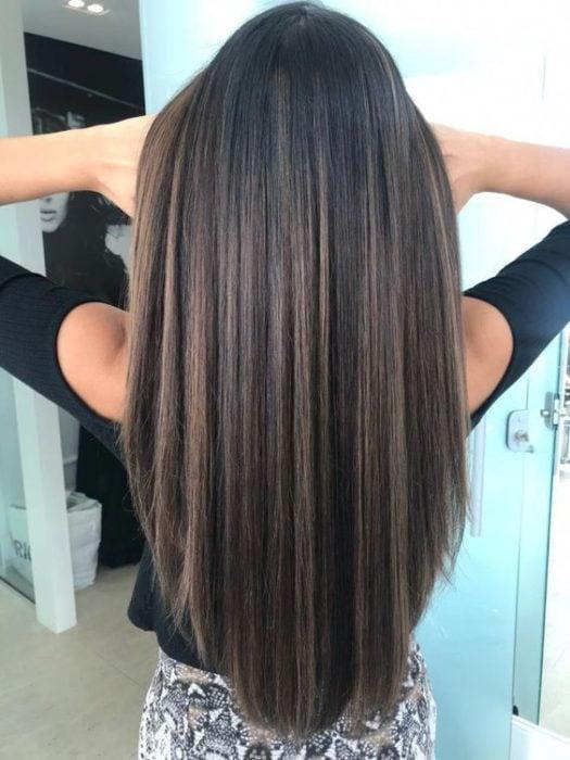 Chica con cabello planchado usando blusa negra