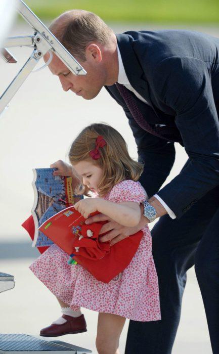 Principe William ayudando a subir los escalones del avión a la princesa Carlota