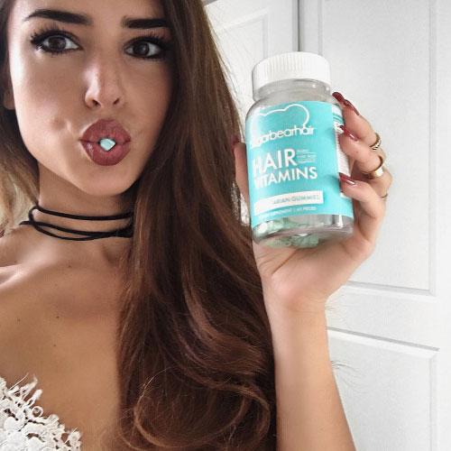 Chica comiendo vitaminas capilares