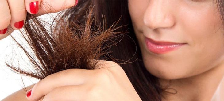 Chica observando las puntas abiertas de su cabello