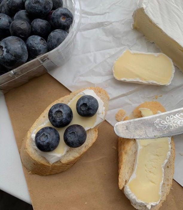 Snack de queso con arándanos frescos sobre una rebanada de pan