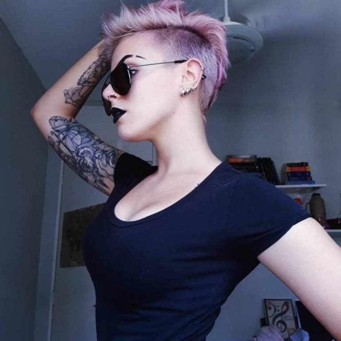 Modelo con corte cabello rapado en tonos violeta, usando gafas de sol negras y blusa entallada del mismo tono