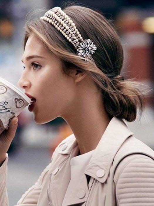 Chica con chaqueta beige tomando café con recogido de cabello adornado con diadema